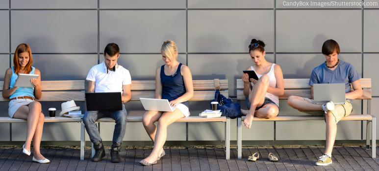 Ragazzi che studiano davanti al PC, seduti su una panchina