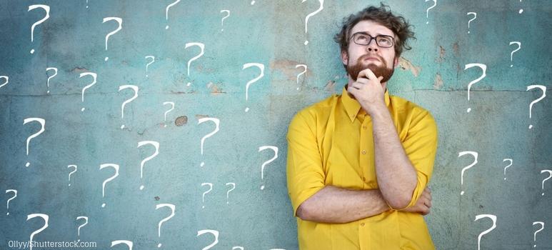 Ragazzo pensieroso circondato da punti interrogativi