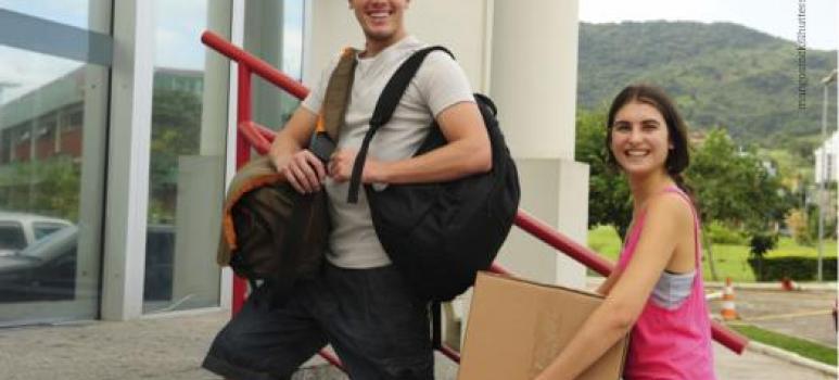 Ragazzo e ragazza sorridenti che entrano in un palazzo, con borse e uno scatolone