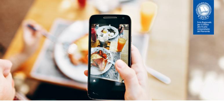 immagine di una mano che fotografa un piatto in tavola